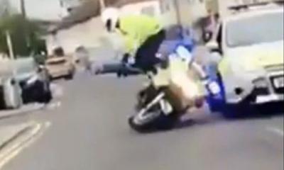 policía es empujado de su moto